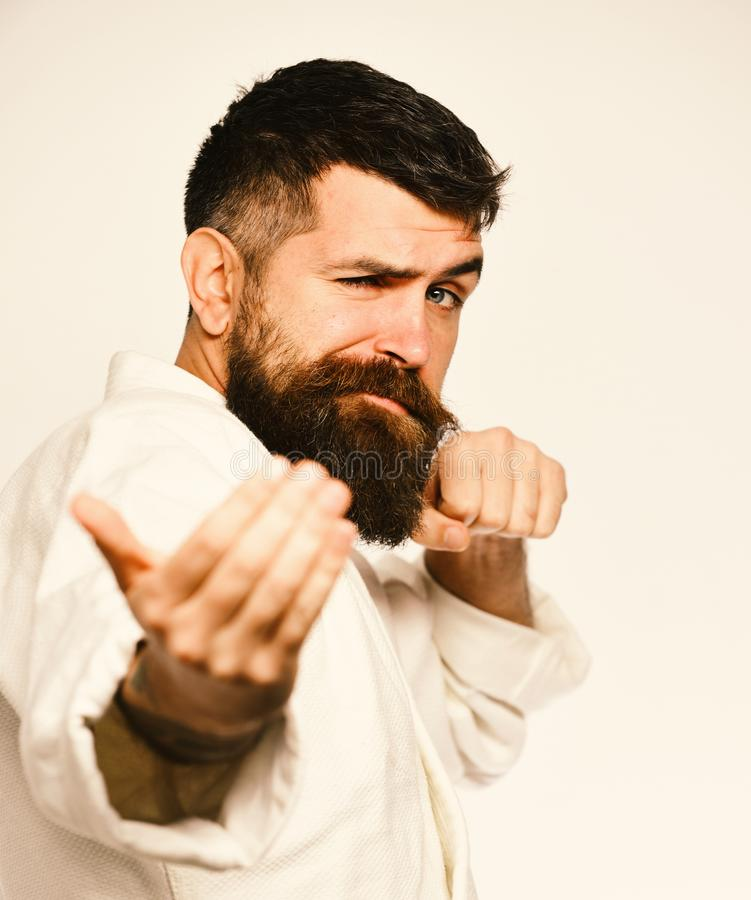 Taekwondo master practices attack and provokes fight. Man with beard in white kimono on white background. Oriental sports concept. Karate man with flirty face royalty free stock images