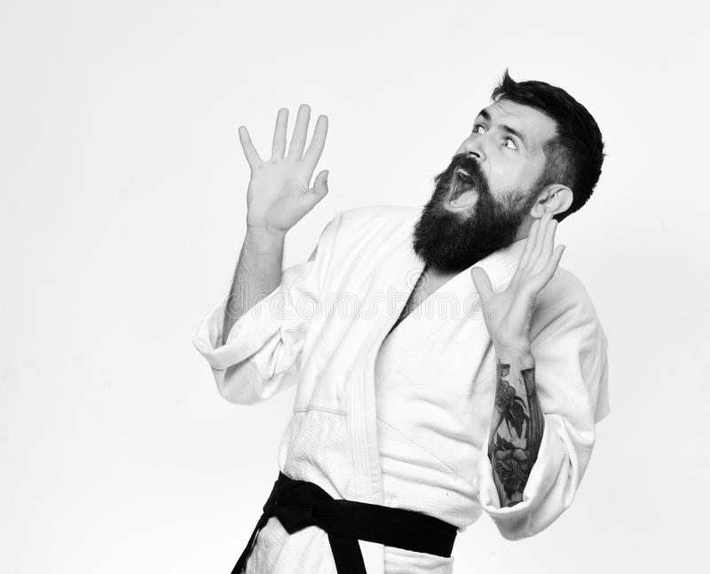 Taekwondo master puts hands up in fear and yells. Karate man with scared face in uniform. Man with beard royalty free stock photo