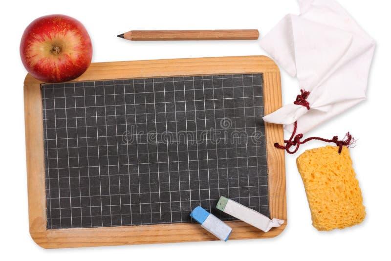 Tafel mit Apfel, Schwamm, Kreide, Stoff und Bleistift stockfotos
