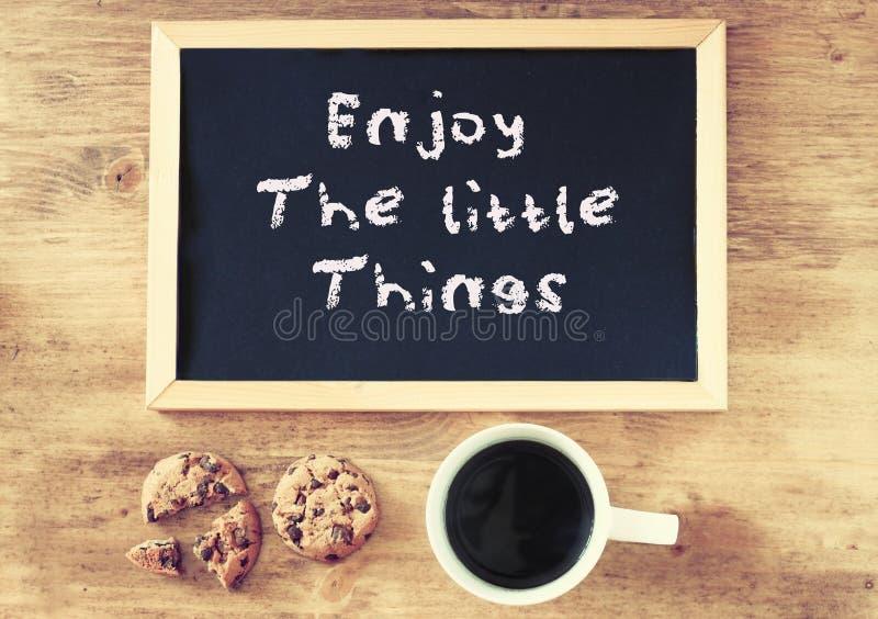Tafel mit der Phrase können Sie alles über hölzernem Hintergrund mit Tasse Kaffee tun lizenzfreie stockfotografie