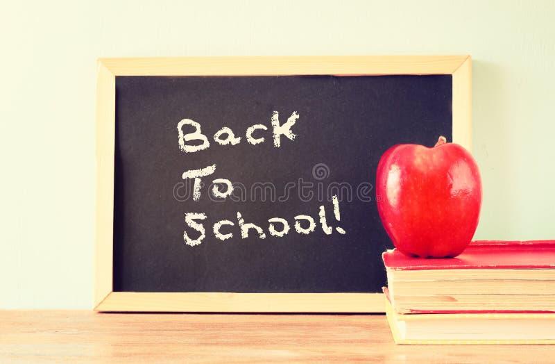 Tafel mit der Phrase zurück zu Schule, Apfel und Stapel Büchern Gefiltertes Bild lizenzfreie stockbilder