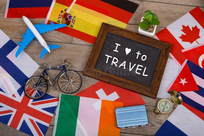Tafel mit Text u. x22; Ich liebe zu Travel& x22; , Flaggen von verschiedenen Ländern, Flugzeugmodell, wenig Fahrrad und Koffer lizenzfreie stockfotos