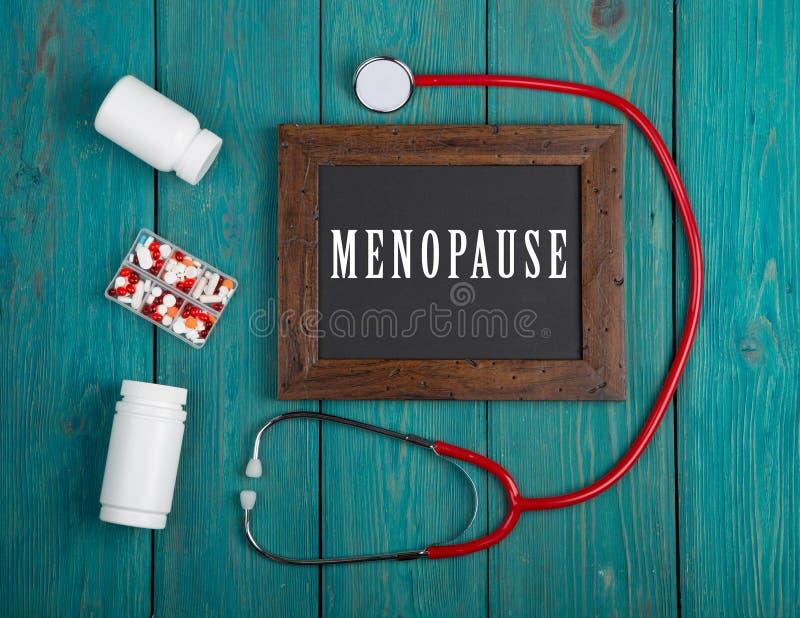 Tafel mit Text u. x22; Menopause& x22; , Stethoskop, Pillen auf blauem hölzernem Hintergrund lizenzfreie stockfotos