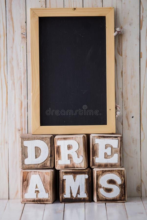 Tafel und TRÄUME unterzeichnen gemacht von den Holzklötzen auf hölzernem backg lizenzfreie stockfotografie