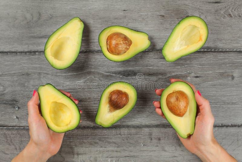 Tafelbladmening, vrouwenhanden die avocado houden die in de helft, zichtbaar zaad rond wordt gesneden, de meer avocado'shelften o stock foto