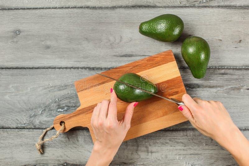 Tafelbladmening, vrouwenhanden die chef-kokmes, scherpe avocado o houden royalty-vrije stock fotografie