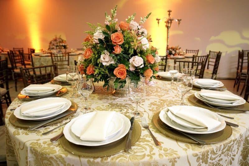 Tafelinstelling met bekers, platen, luiers en levensmiddelen, plaatsing van de bloem in het midden met een vervaagde achtergrond stock foto