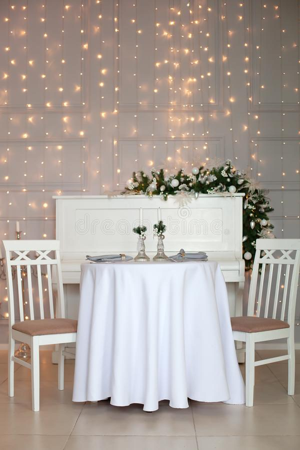 Tafelinstelling voor kerstdiner Festive table setting with tablecloth between winter decorations and white candles Kerstmis royalty-vrije stock foto's