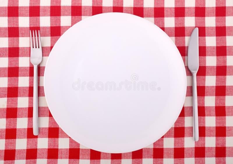 Tafelkleed met vork, mes en een lege plaat stock foto's