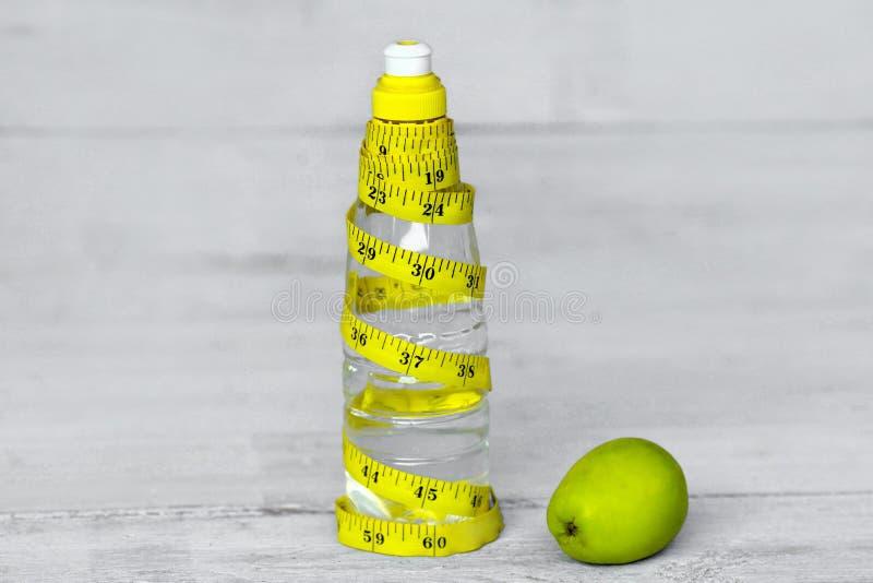 Tafelwasser für gesundes Leben über gelbem messendem Band und grünem Apfel lizenzfreie stockfotos