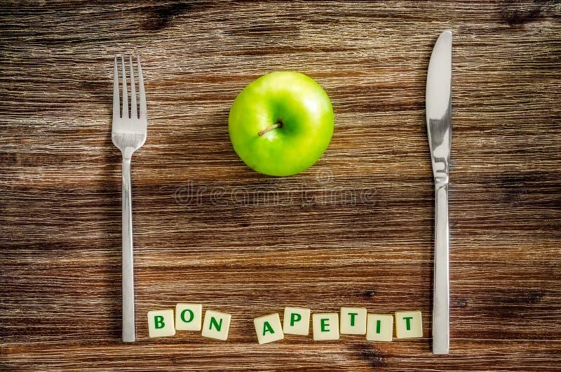 Tafelzilver en appel op houten lijst met het teken van Bon apetit royalty-vrije stock fotografie