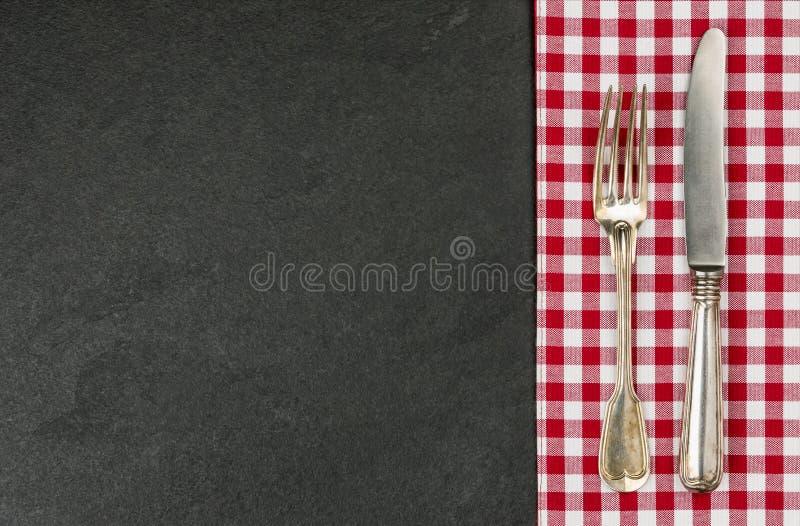 Tafelzilver op een leiplaat met een rood geruit tafelkleed royalty-vrije stock foto's