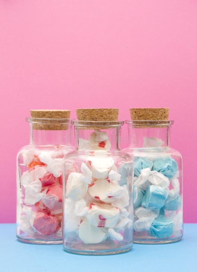 Taffy branco e azul vermelho da água salgada no frasco arrolhado fotografia de stock royalty free