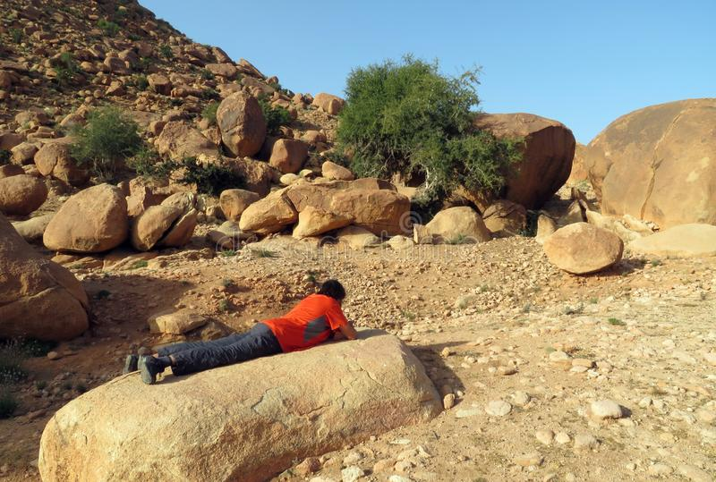 A hiker taking a break in the mountains of Morocco, lying on a stone looking at his smartphone. Tafraout, Morocco - February 22, 2019: A hiker taking a break in stock image
