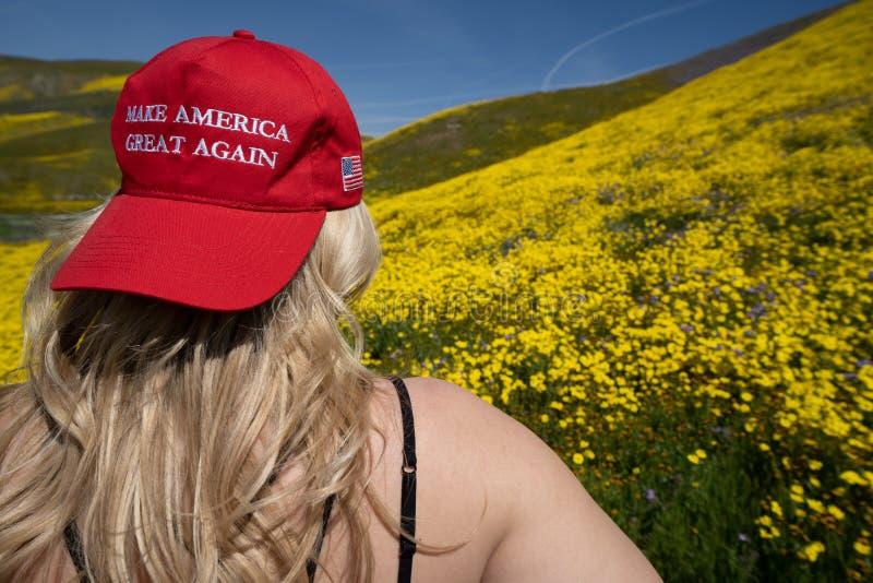 Taft, Калифорния - 25-ое марта 2019: Белокурая женщина нося Дональд Трамп делает Америкой большую снова шляпу, сидя в поле желтог стоковое фото rf
