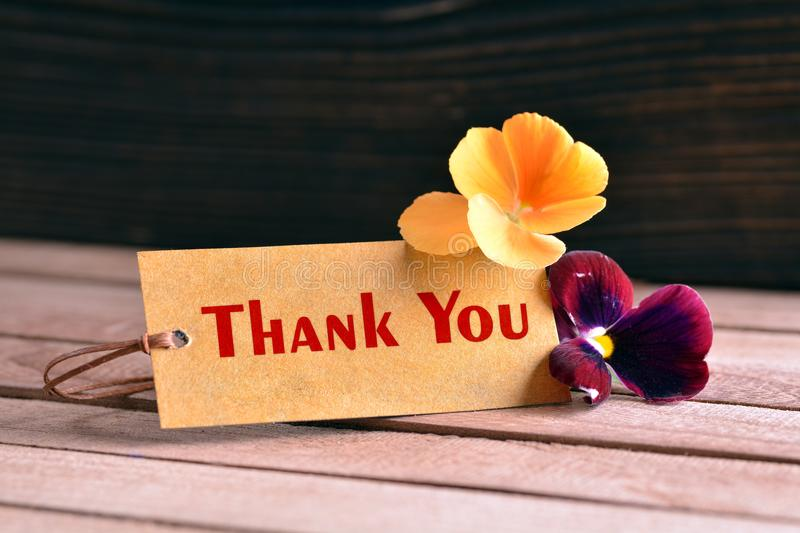 Thank you tag. Tag banner thank you and violet flower on wooden desk royalty free stock photo