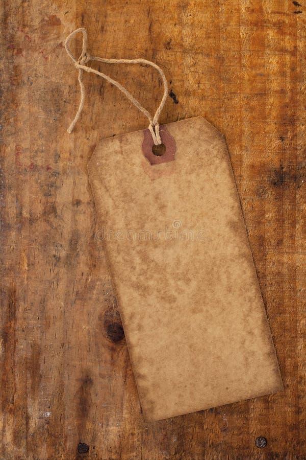 Tag de papel velho com corda na tabela de madeira do grunge fotos de stock royalty free