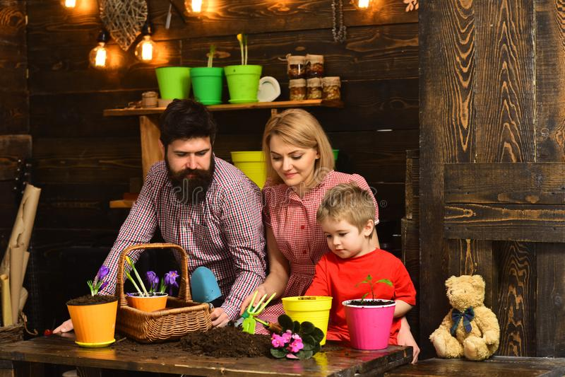Tag der Erdekonzept Familie setzen Blume im neuen Topf am Tag der Erde wieder ein Kinderjunge mit Mutter und Vater Potting blühen stockbild