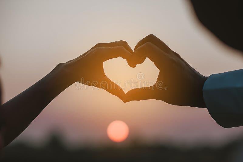 Tag der Liebe der jungen Hand mit dem Herzen von zwei Leuten lizenzfreies stockfoto