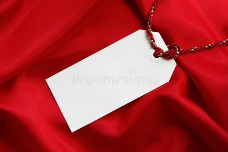 Tag do presente no cetim vermelho imagem de stock royalty free