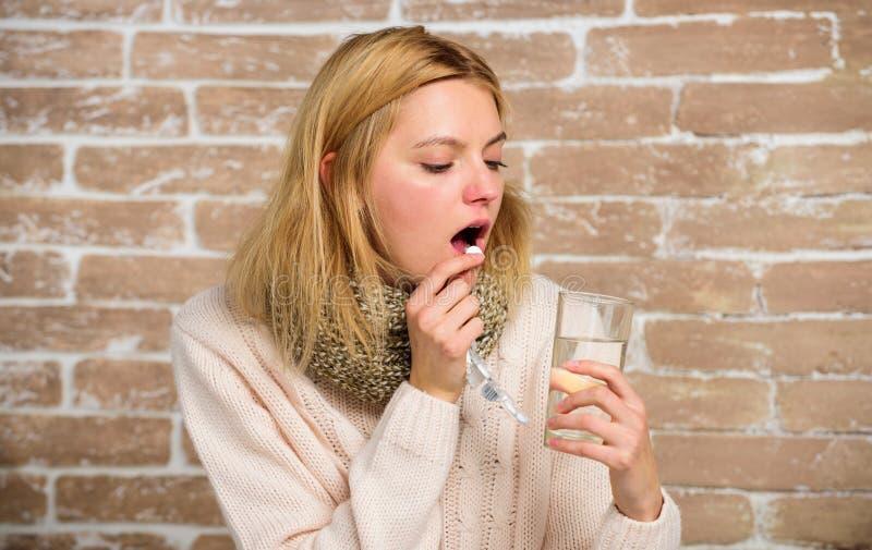 Tagandeläkarbehandlingar som förminskar feber Huvudvärk- och feberboter Kvinnan rufsade till glass vatten och minnestavlor för hå arkivbild