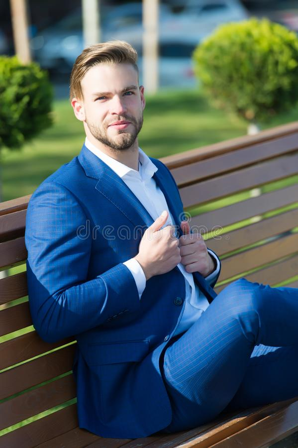Tagandeminut som förnyar tankar Mannen i affärsdräkt kopplar av sitter bänken parkerar in Formellt klädframstickande för affärsma arkivfoton