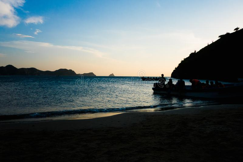 TAGANGA,哥伦比亚- 2017年10月19日:未认出的人的阴影在一条小船里面的在美丽的日落期间 免版税库存图片