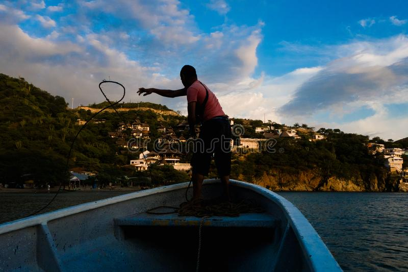 TAGANGA, COLOMBIA - OCTOBER 19, 2017: Shadow of unidentified man inside of a boat during a sunset at the beautiful. Caribbean beach in Taganga, Colombia royalty free stock photography
