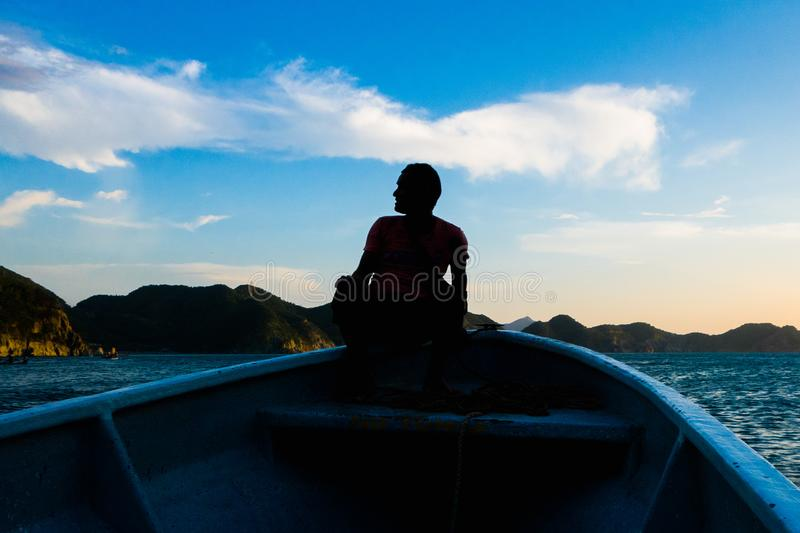 TAGANGA, COLOMBIA - OCTOBER 19, 2017: Shadow of unidentified man inside of a boat during a sunset at the beautiful. Caribbean beach in Taganga, Colombia stock images