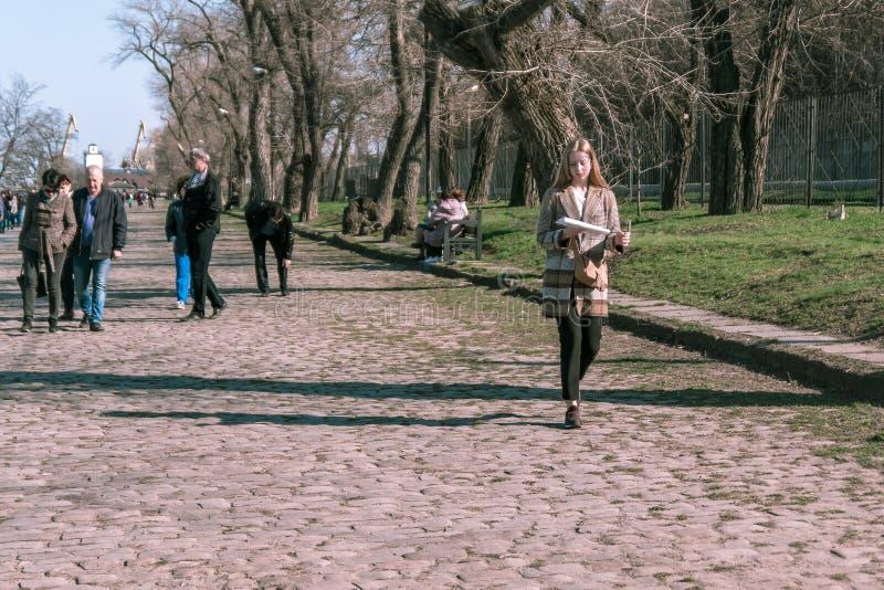 Taganrog, Rusia - 07 04 19: chica joven hermosa que lee en camino en el parque imagen de archivo