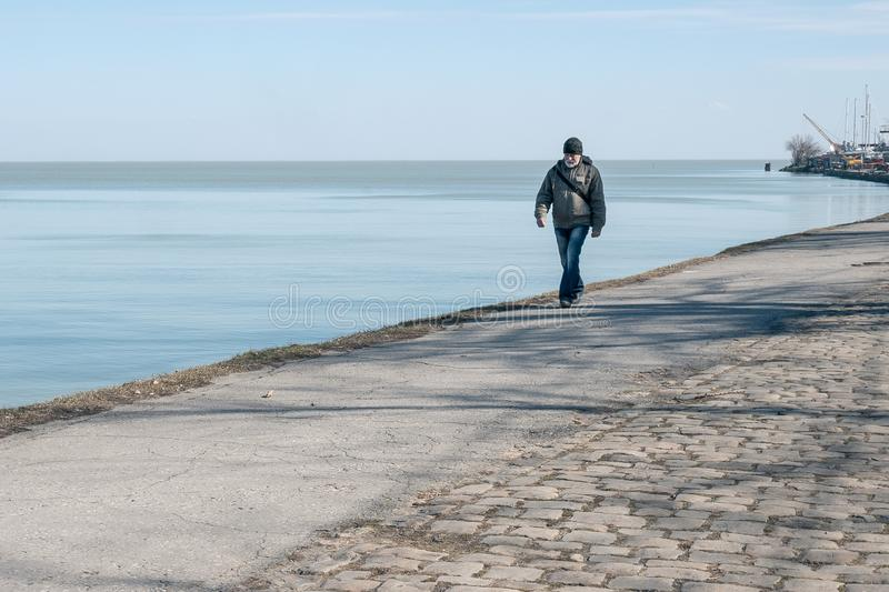 Taganrog, Russia - 05.03.19: grandfather with a gray beard walks along the promenade. royalty free stock image