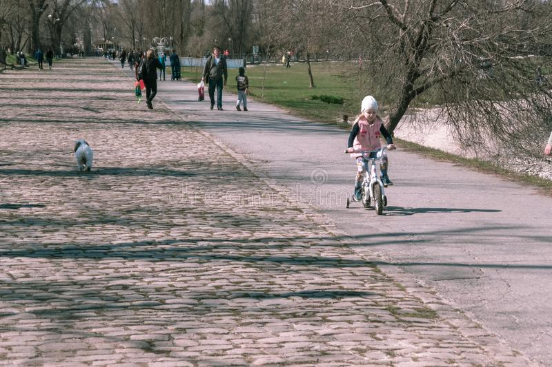 Taganrog, Russia - 07.04.19: little girl in a pink jacket rides a bicycle. royalty free stock photos