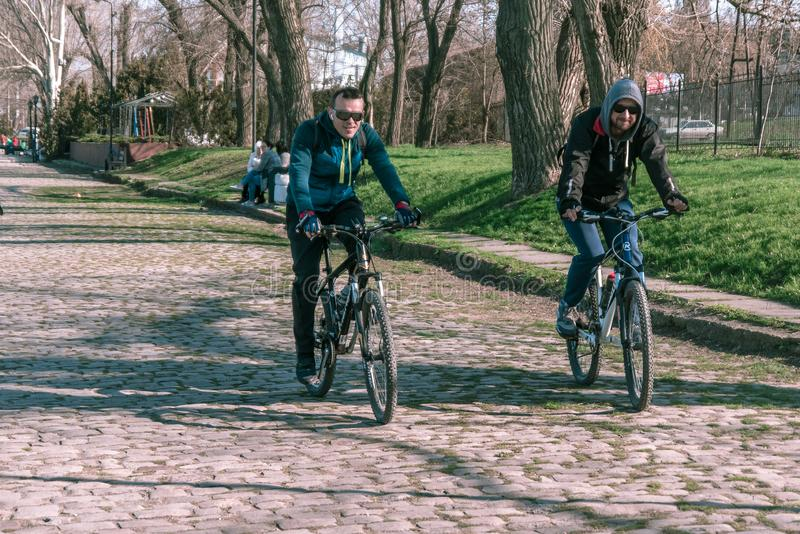 Taganrog, Russia - 07.04.19: wo cheerful men ride bicycles on stone pavement in sunny weather. Two joyful friends ride bicycles in the park in spring royalty free stock image