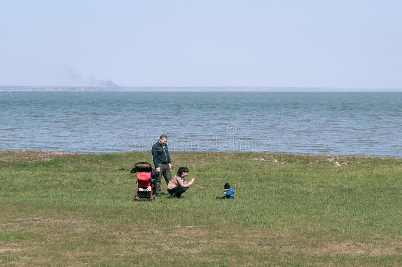 Taganrog, Russia - 07.04.19: young family resting with a child on a green lawn near the sea. stock photography