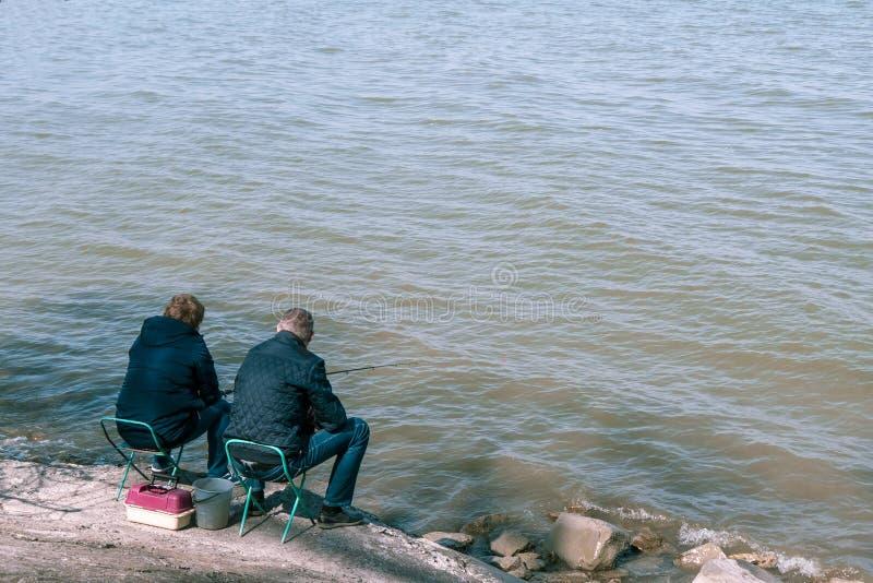 Taganrog Ryssland - 07 04 19: två personer i omslag sitter och fiskar arkivfoto