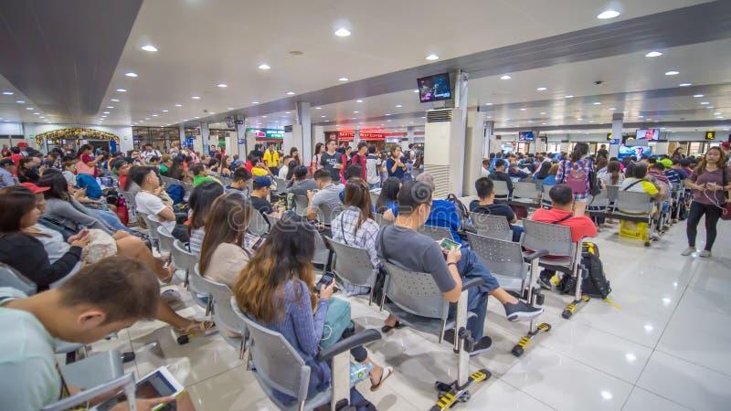 Tagbilaran Filippinerna - Januari 5, 2018: Passagerare som väntar på avvikelse på flygplatsen royaltyfria foton