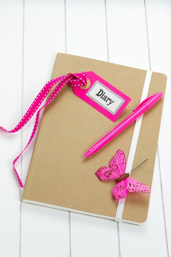 Tagebuch mit rosa Dekorationen auf Holzoberfläche stockfotos