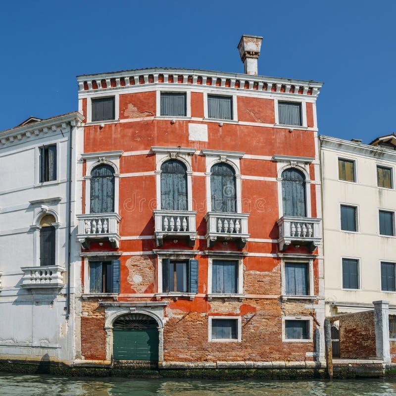 Tageslichtansicht zum roten historischen Gebäude auf einem venetianischen Kanal stockfotografie