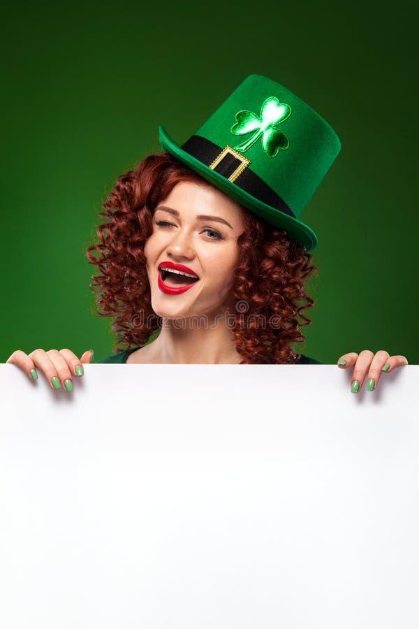 Tagesshamrocks und -rosen Str Junger glücklicher Oktoberfest-Kobold, einen grünen Hut mit Klee tragend, dienende große Bierkrüge  lizenzfreies stockbild