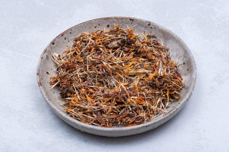 Tagete messicano dei semi asciutti del tagete, tagete azteco, tagete africano in piatto ceramico su grigio Tagetes Erecta dais fotografia stock