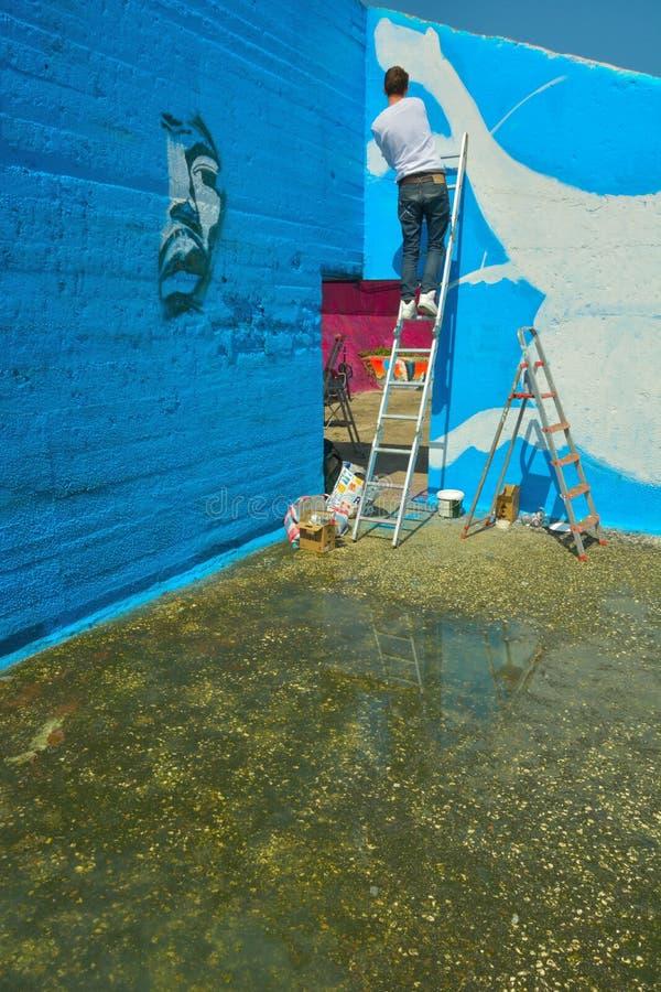 Taggers- och grafittikonstnär på arbete som gör vibrerande konstverk royaltyfri bild