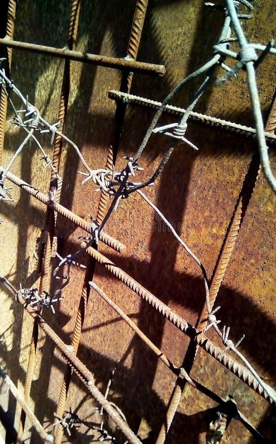 Taggtråd på metallförstärkningen på en bakgrund av rostigt järn arkivbild