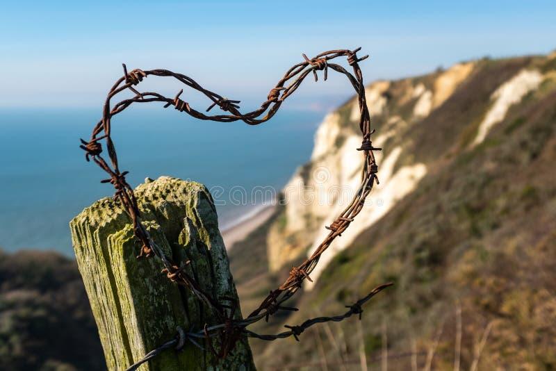 Taggtråd som formas in i en hjärta med en kuliss av vita klippor i Devon royaltyfri fotografi