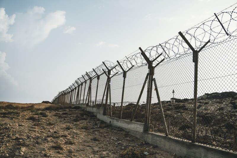 taggtrådstålvägg mot immigationsna Vägg med taggtråd på gränsen av 2 länder Privat eller stängd militär arkivbild
