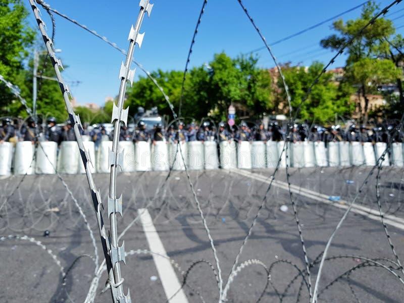 Taggtrådstaketet ställde in vid polisen under en tumult royaltyfri foto