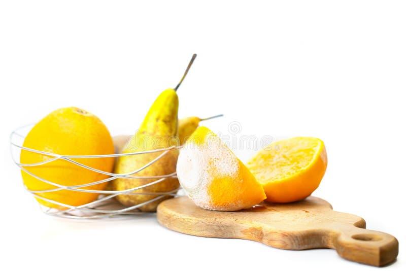 Tagli in arancia guastata mezza con la muffa bianca e verde, contro lo sfondo di altri frutti immagine stock libera da diritti