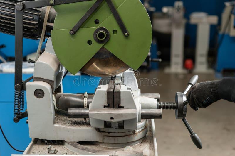 Tagli del lavoratore un il pezzo di materiale con una macchina circolare della sega Ingegnere industriale che lavora a tagliare u fotografia stock libera da diritti