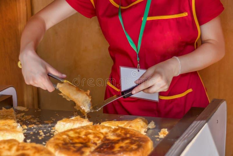Tagli della lavoratrice un burek del Balcani con formaggio nel negozio del forno fotografia stock