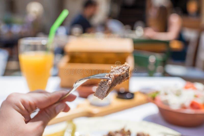 Tagli di agnello arrostiti affettati su una forcella La donna ha una cena in una locanda greca fotografia stock