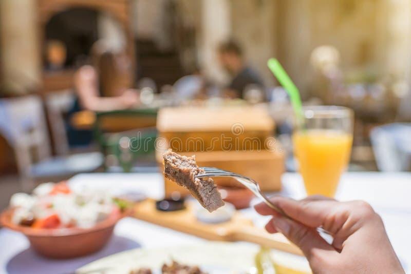 Tagli di agnello arrostiti affettati su una forcella La donna ha una cena in una locanda greca immagini stock